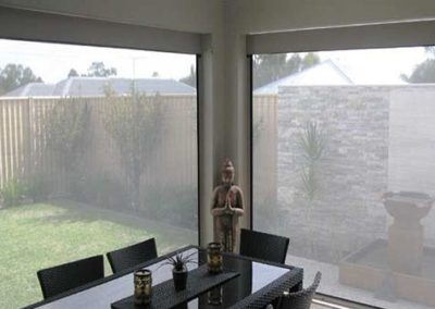 View from the inside of a house through windows with sheer external blinds with a dining table in front of the windows.