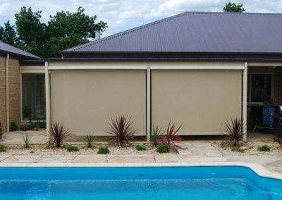 A pool is in front of house with beige External Blinds
