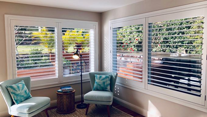 Beautiful white wooden plantation shutters installed in a living room with dark wood flooring, teal armchairs and a floor lamp.