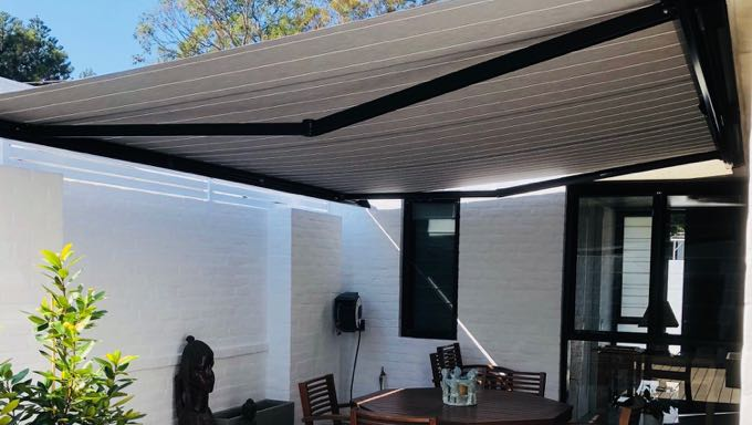 Picture of white awning covering patio area with a wooden table, wooden chairs and white walls.