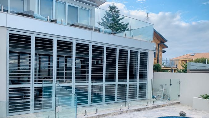 Aluminum shutters lining the windows of a modern home, opened and looking out to the pool area.