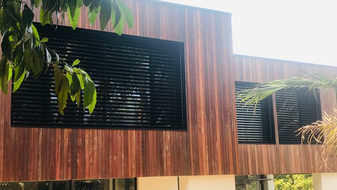 Black aluminum venetian blinds on the windows of a beautiful home with a variety of wood panels on its exterior.
