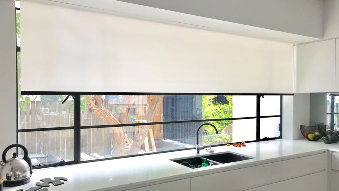 Roman roller blinds extended half-way in the window of a modern kitchen with a white marble bench top.
