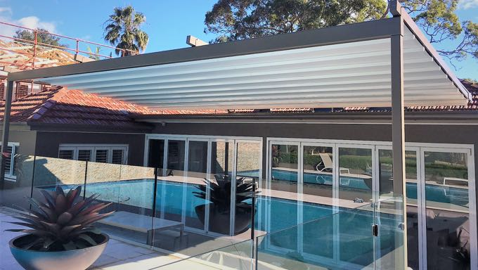 Modern white roof system covering a patio with glass sliding doors and glass panels surrounding the pool.