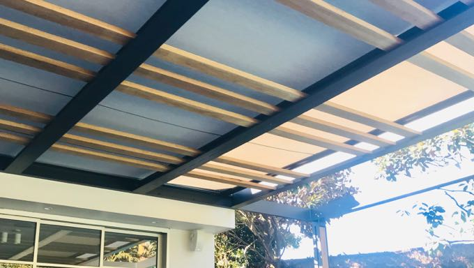 A Varioscreen (retractable sunroof) patterned with wooden panels and black metal, covering a sunny patio
