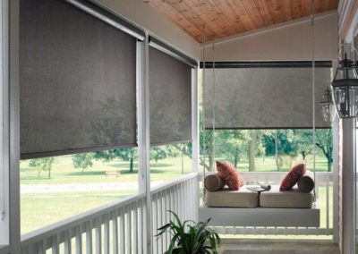A view of external blinds from inside a covered patio with white wood fencing and a white porch swing with a variety of pillows.