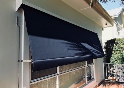 Black external blinds fully extended, covering the window and contrasting with the white walls of the house.