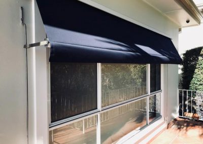 Black external blinds partially extended over the window, and contrasting with the white walls of the house