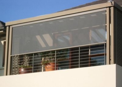 Sheer external blinds fitted along a covered balcony, pulled down to the metal railing of the balcony.