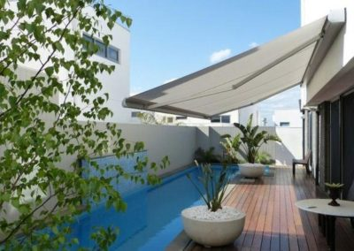 Beautiful folding-arm-awnings-over pool and the outdoor are with timber floors