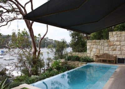 Dark grey folding-arm-awnings installed over outdoor and pool area with view on to Pittwater