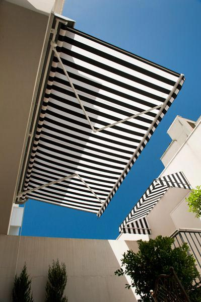 Frog perspective of a high quality black and white striped folding-arm-awnings