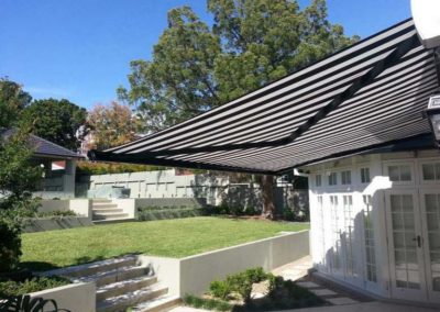 folding-arm-awnings throwing shade over garden area