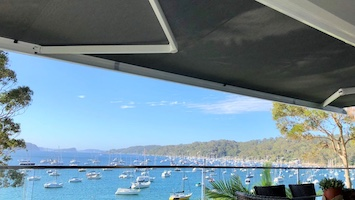 A motorised awning set upon an entertaining area overlooking a harbour with multiple sailing boats, blue skies and a bushy headland