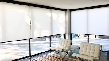 White fabric roller blinds, semi-covering two full sized window walls from the sun, in a room with two beige leather chairs