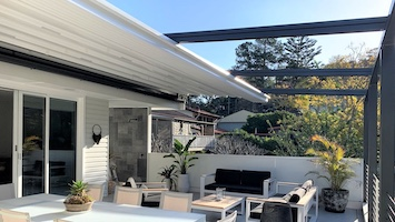 Outdoor patio half covered with a retractable roof system with the afternoon light shining on the outdoor furniture