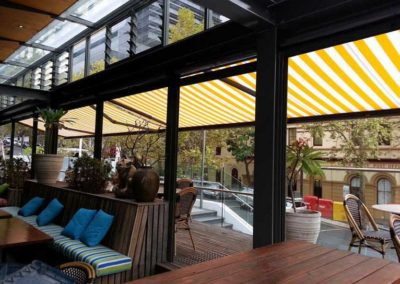 yellow white striped folding-arm-awnings installed over balcony area
